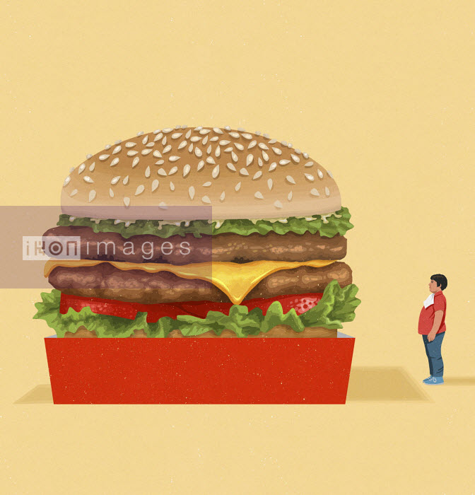 Overweight boy looking at giant cheeseburger - John Holcroft