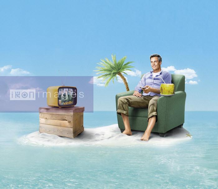 Happy man stranded on desert island watching television - Thomas Kuhlenbeck