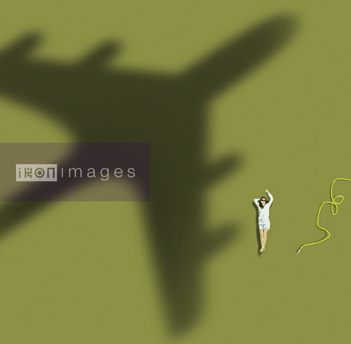 Woman relaxing on lawn waving at passing aeroplane - Gary Waters