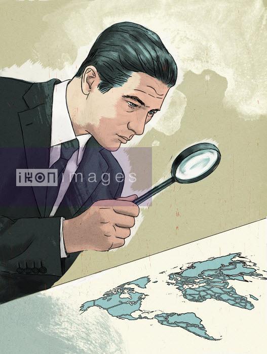 Businessman examining map of the world through magnifying glass - Thomas Kuhlenbeck