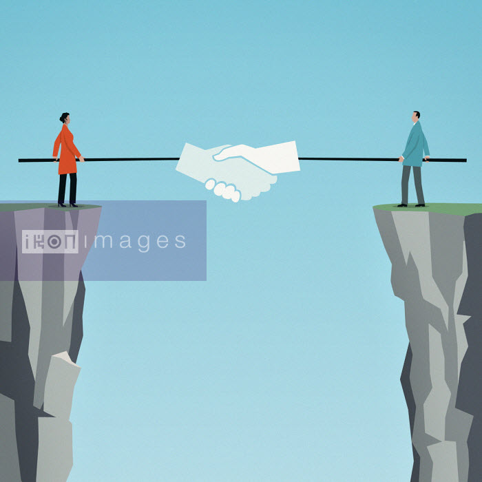 Businessman and businesswoman shaking hands with poles over gap between cliffs - Mark Airs