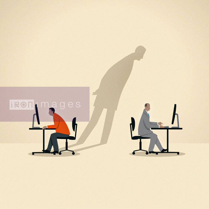 Shadow of businessman spying on colleague using computer - Mark Airs
