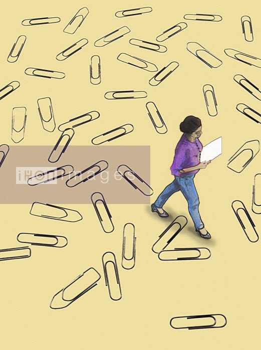 Woman walking over lots of paperclips - Gary Waters