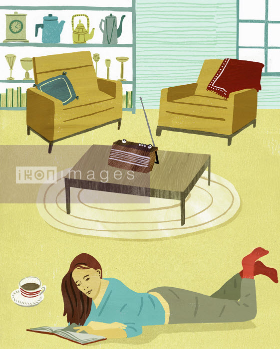 Woman lying on floor in living room reading - Daniel Haskett