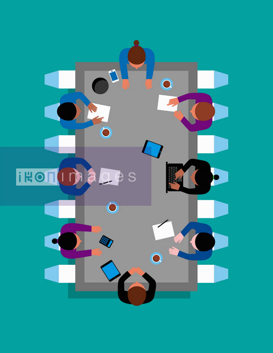 Business people sitting around microchip meeting table - Patrick George