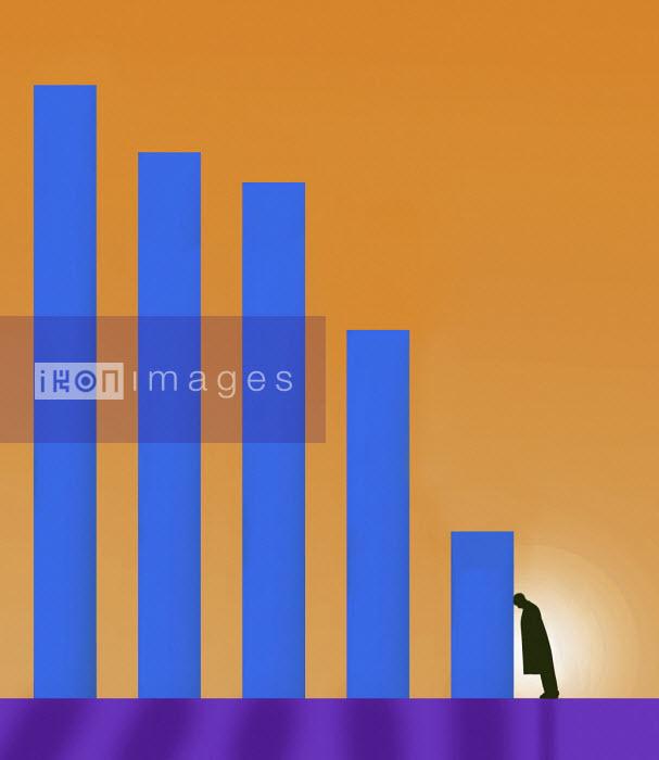 Businessman slumped in despair against falling bar chart - Gary Waters
