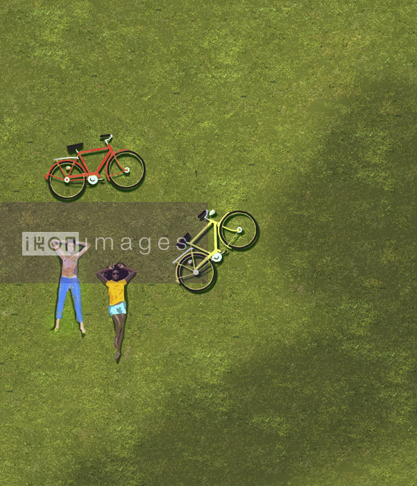 Overhead view of couple sunbathing on grass beside bicycles - Gary Waters