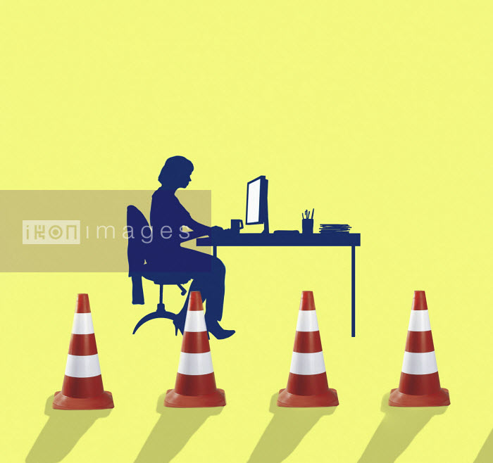Businesswoman working at desk behind traffic cones - Gary Waters