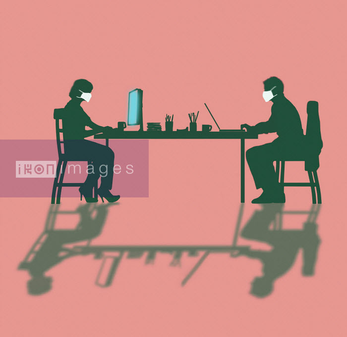Businessman and businesswoman working at desk wearing face mask - Gary Waters