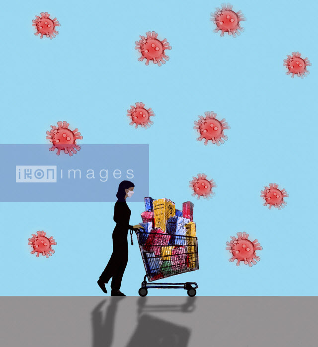 Woman wearing mask pushing supermarket trolley - Gary Waters
