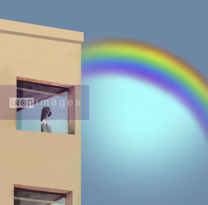 Woman in lockdown looking at rainbow through window - Gary Waters