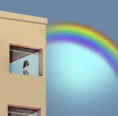 Woman in lockdown looking at rainbow through window